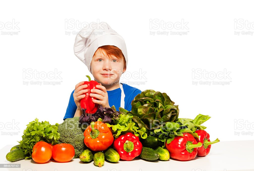 Redheaded boy in cook's uniform holding red pepper stock photo