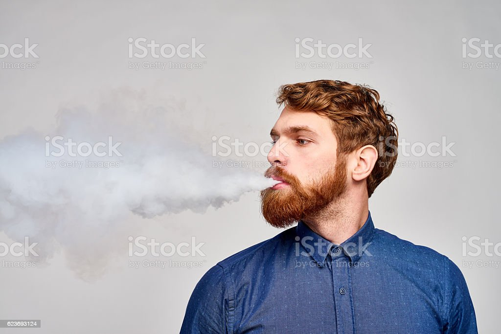 Red-headed smoker looking away stock photo