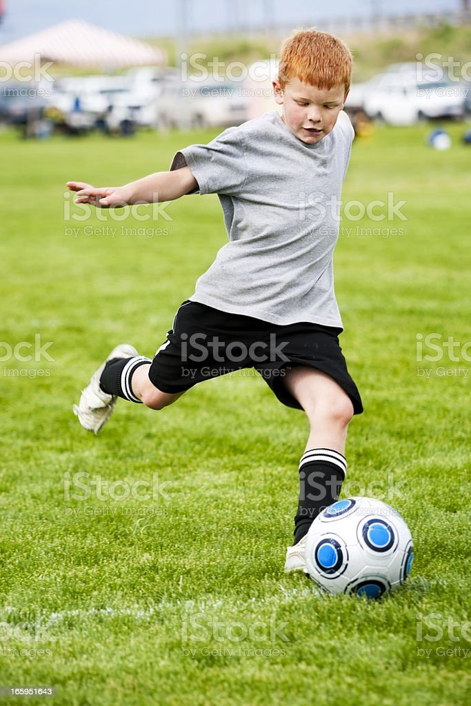 Redheaded Soccer Boy Glides into Fluid Approach Kicking Ball royalty-free stock photo