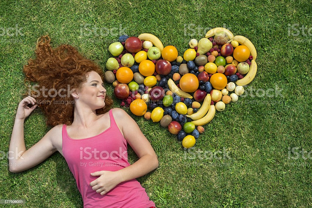 Redheaded woman next to a heart shape made out of fruit stock photo