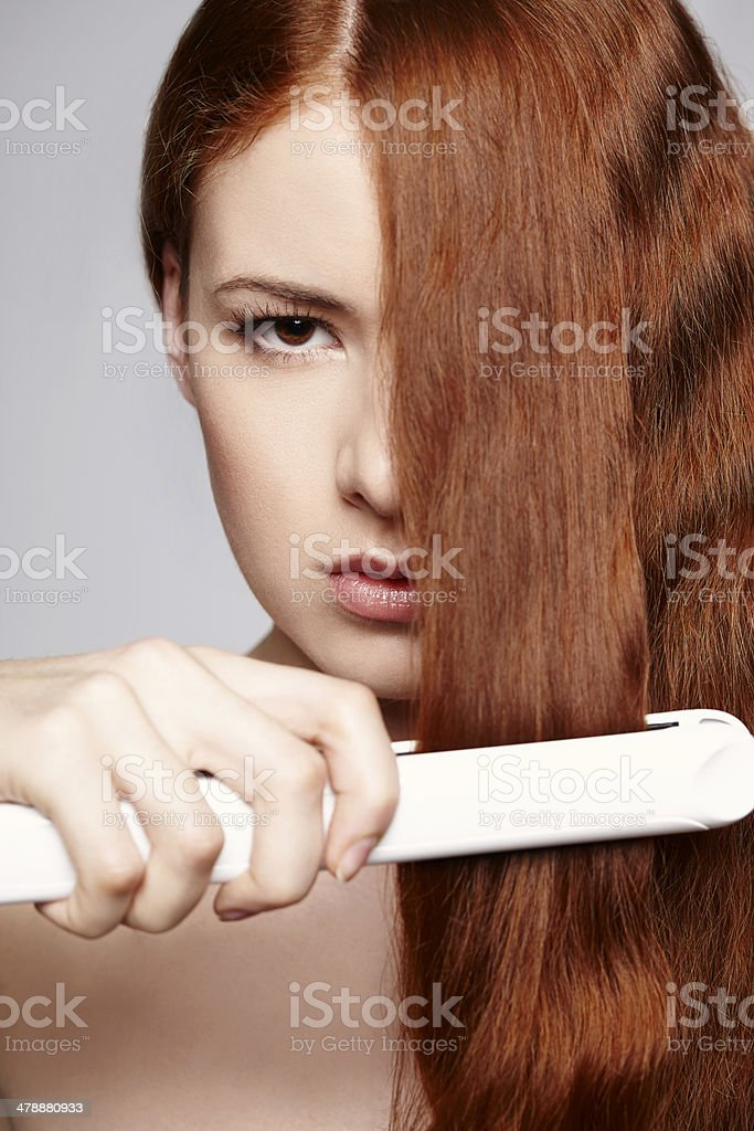 Redheaded woman with hair straightening irons stock photo