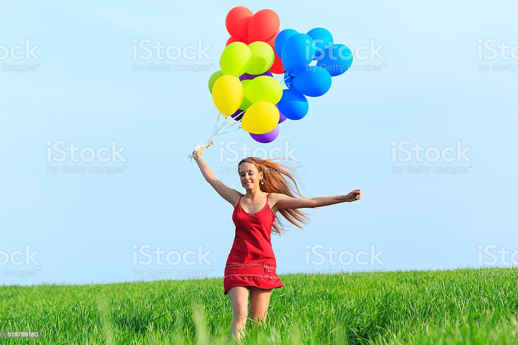 Redheaded young woman with colored balloons jumping stock photo