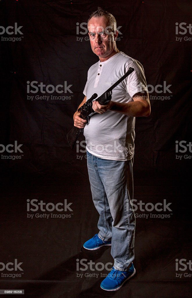 Redneck gunman holding rifle stock photo