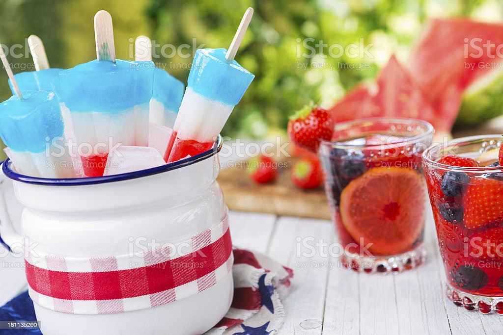 Red-white-and-blue popsicles on an outdoor table with summer drinks stock photo