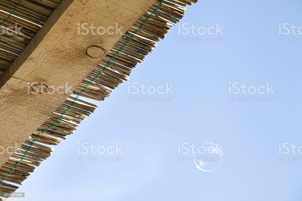 reed and wooden roof with soap bubble stock photo