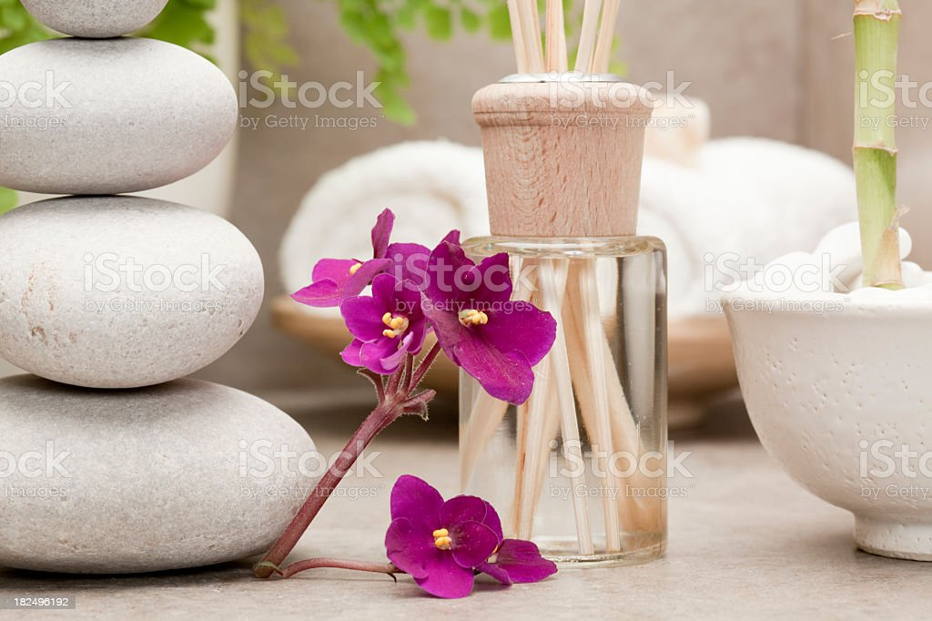 reed diffuser beside african violet flowers stock photo