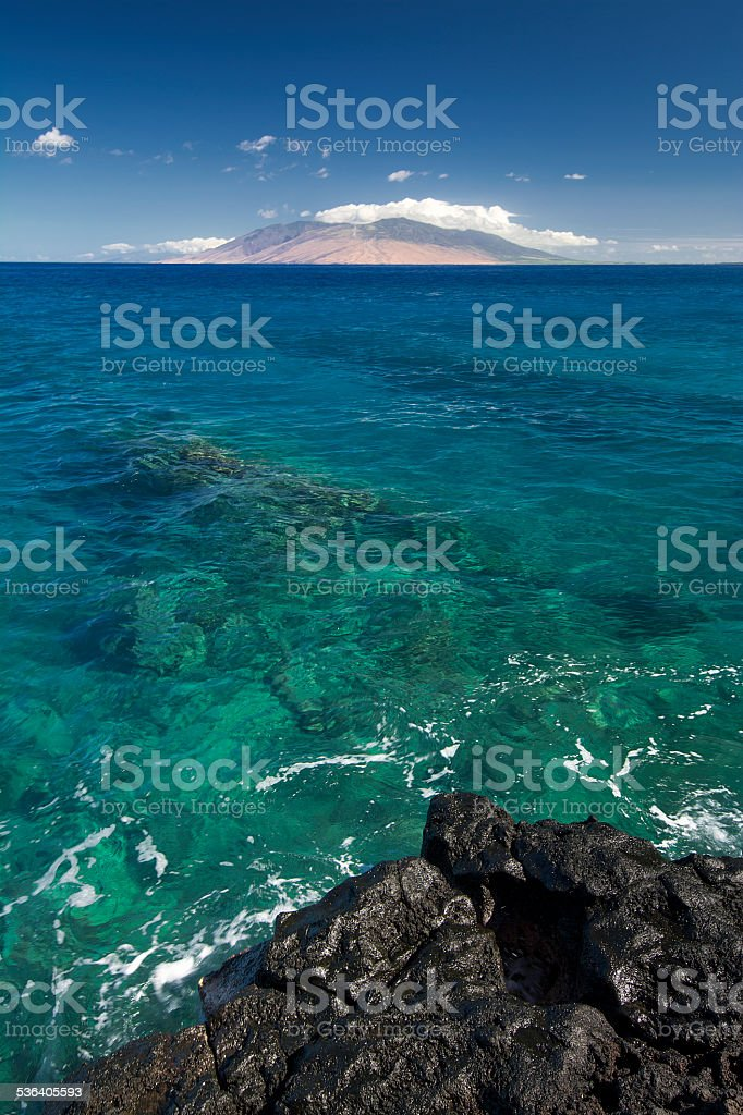 Reef in clear water with West Maui Mountains, Hawaii, USA stock photo