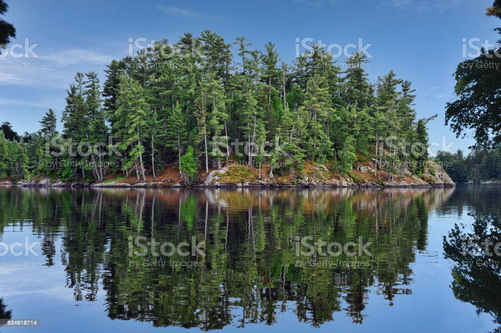 Refection of island in water stock photo