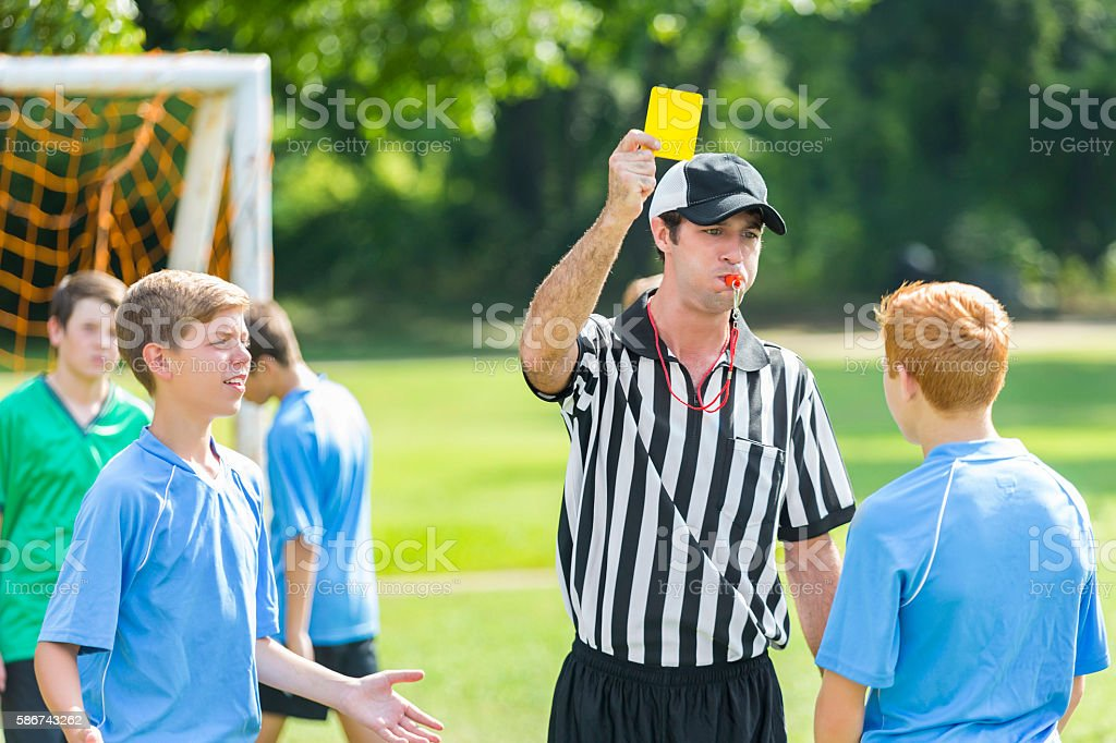Referee gives out yellow card during soccer game stock photo