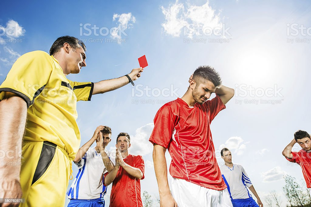 Referee giving red card to soccer player. stock photo
