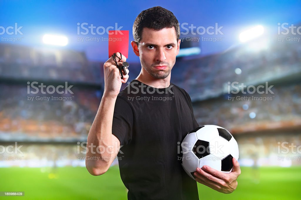 A referee holding a red card and football royalty-free stock photo
