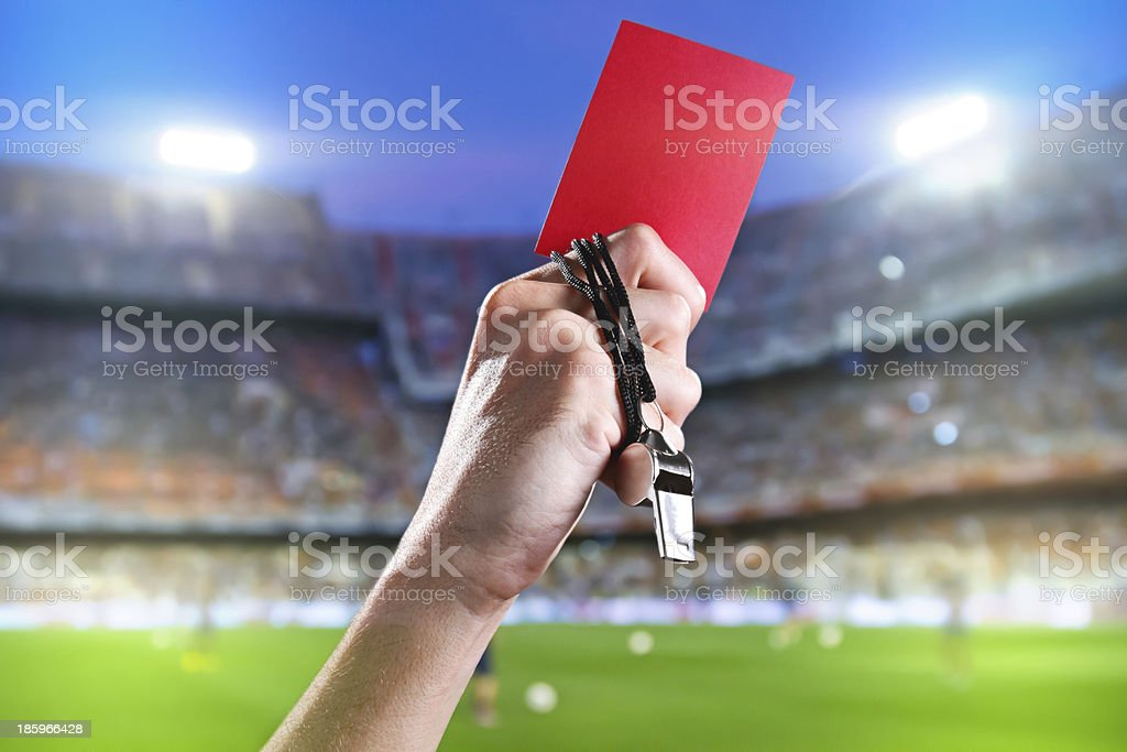 Referee holding up a red card and whistle inside a stadium stock photo