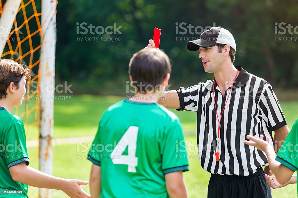 Referee holds up red card in soccer game stock photo