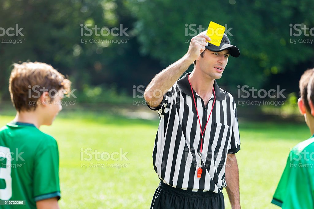 Referee holds up yellow card at soccer game stock photo
