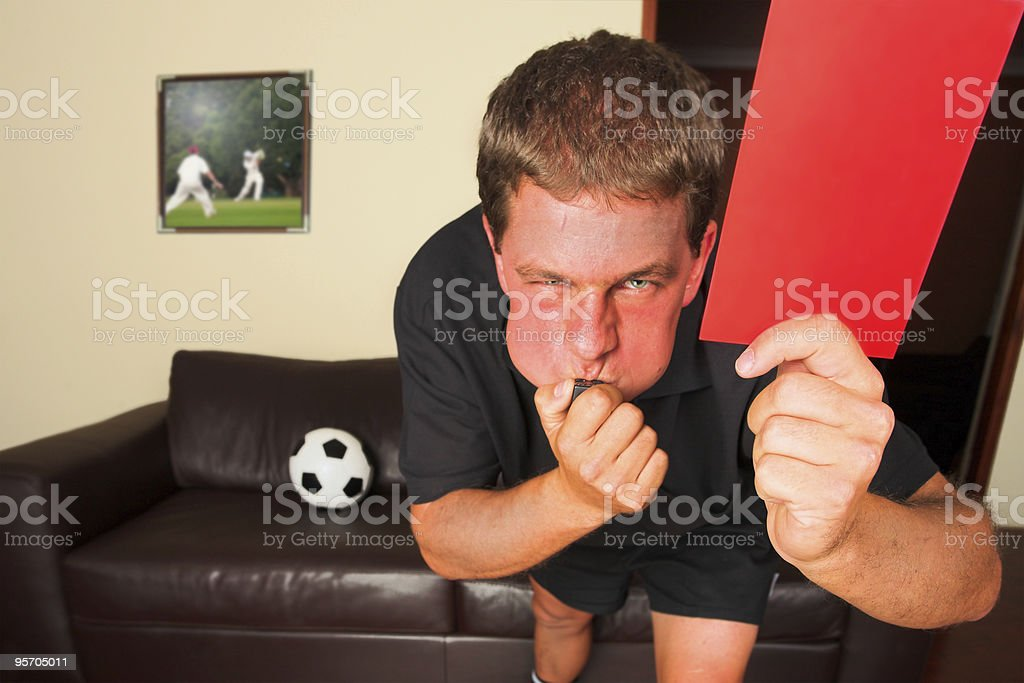 Referee in sitting room blowing whistle with red card royalty-free stock photo