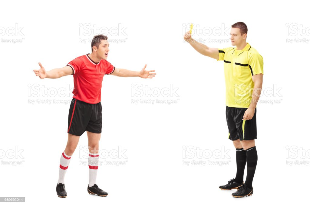 Referee showing a yellow card to a player stock photo