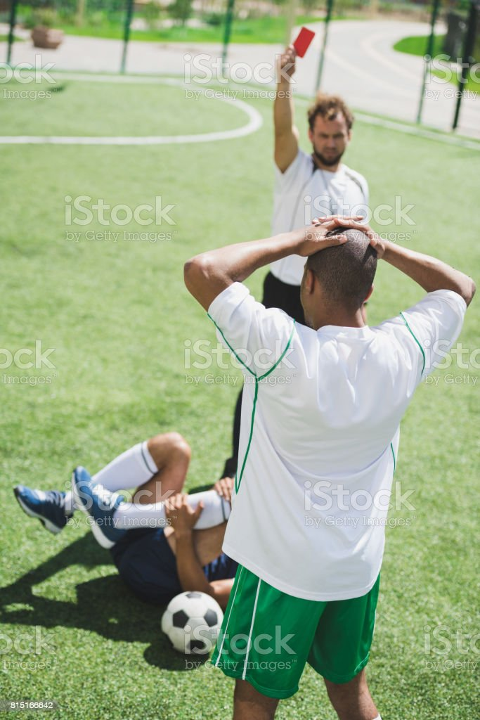 referee showing red card to soccer player during soccer match stock photo