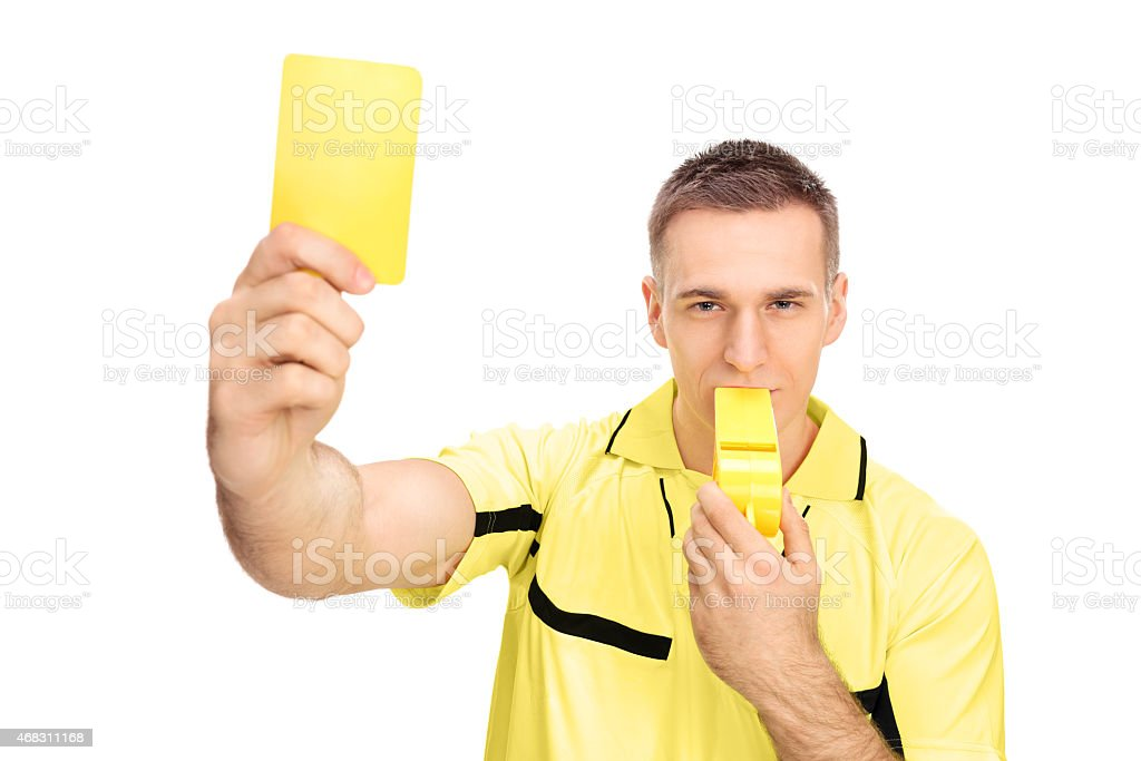 Referee showing yellow card and blowing huge whistle stock photo
