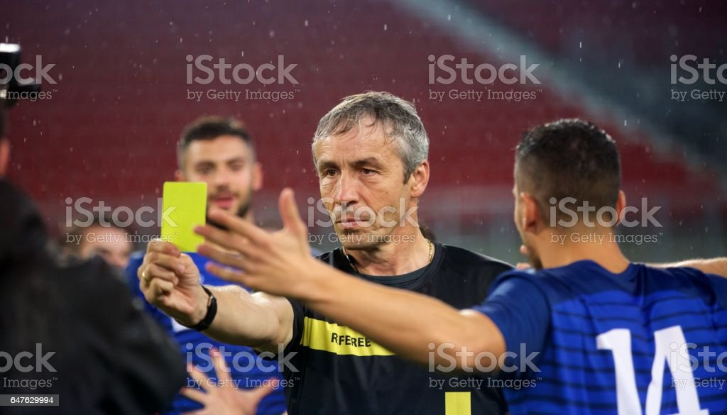 Referee showing yellow card stock photo