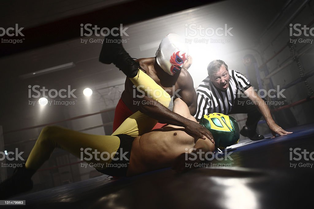 Referee watches as two masked wrestlers fight stock photo
