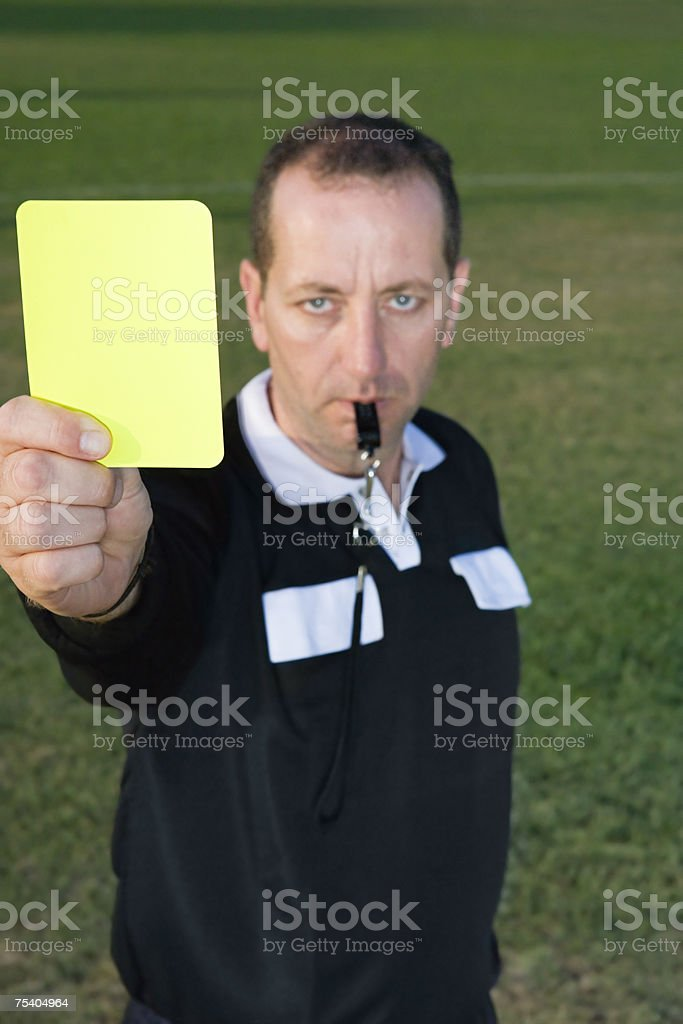 Referre holding yellow card stock photo