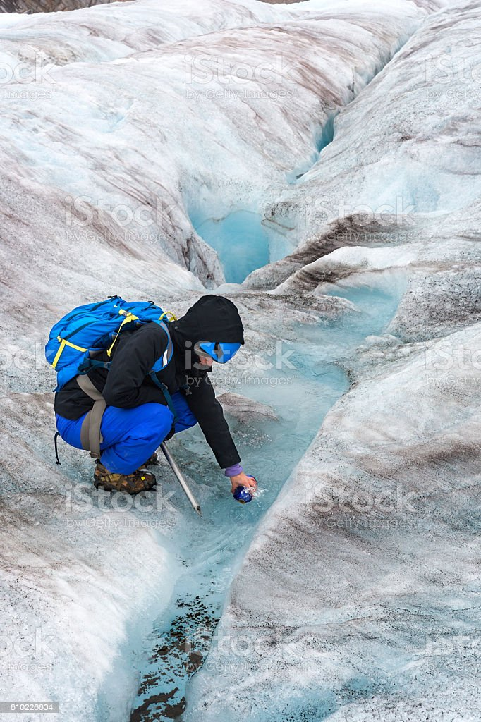Refilling bottle with icy glacial water stock photo