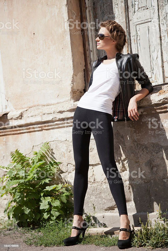 Refined young woman in sunglasses posing near shabby facade stock photo