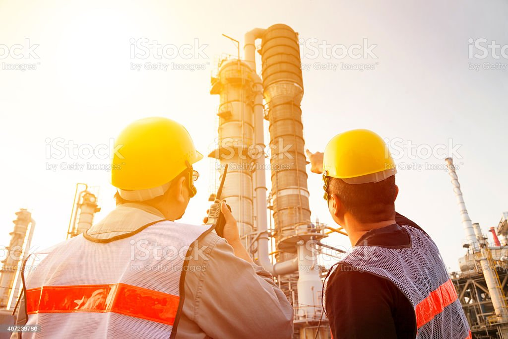 refinery workers discussion and pointing for inspection stock photo