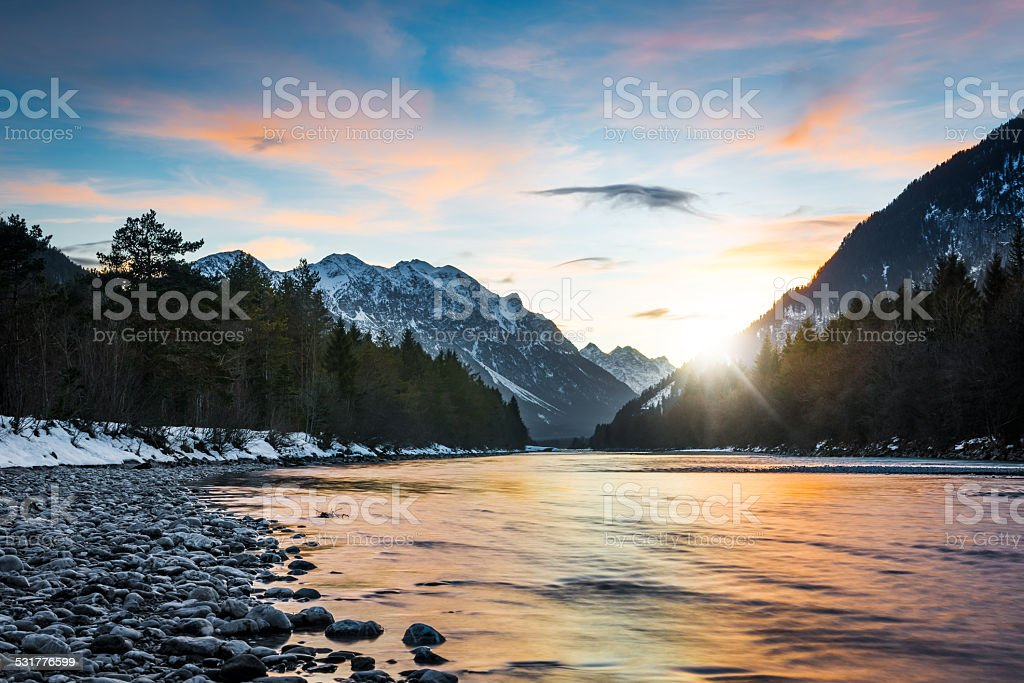 reflecting colors of sunset clouds in rural river stock photo