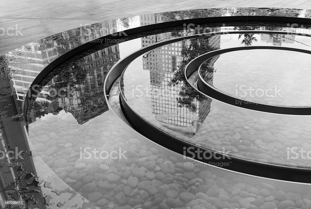 Reflecting image of buildings in a fountain stock photo