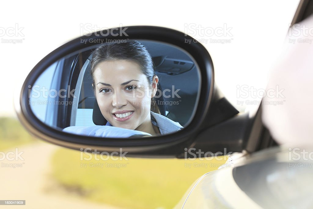 Reflection face of a young girl in the car mirror. royalty-free stock photo
