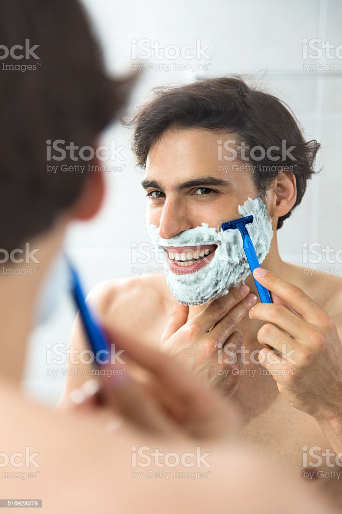 Reflection in a mirror of happy man shaving him self. stock photo