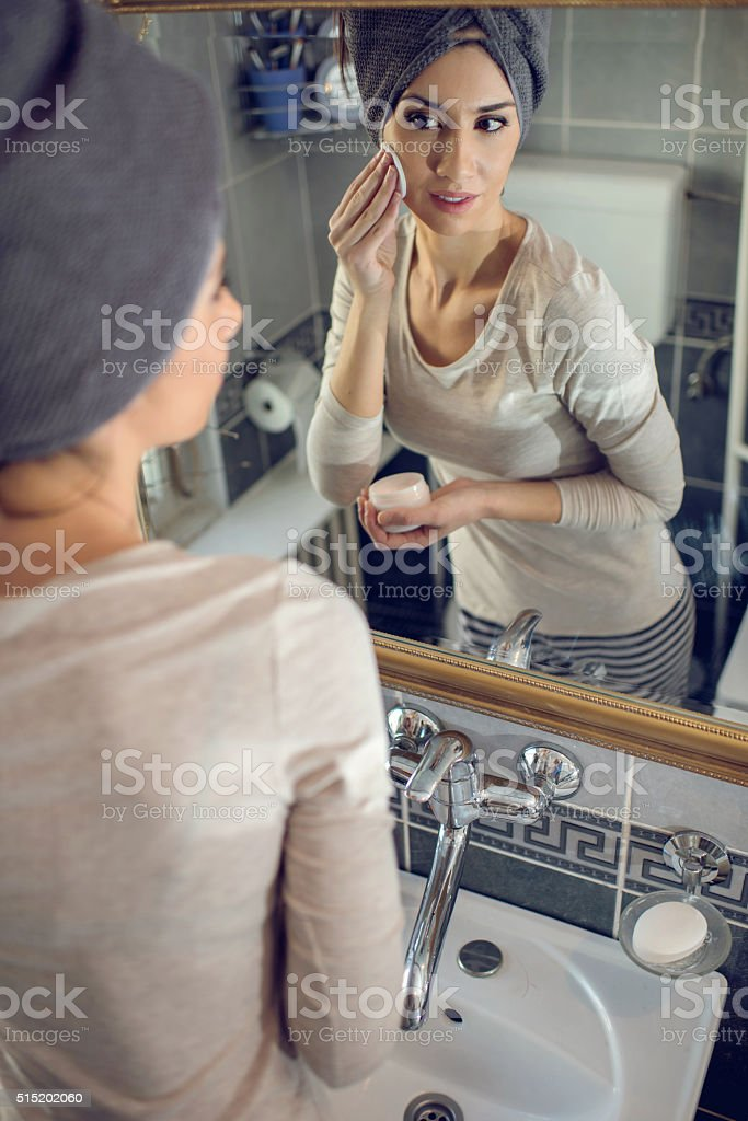 Reflection in a mirror of woman cleaning face in bathroom. stock photo