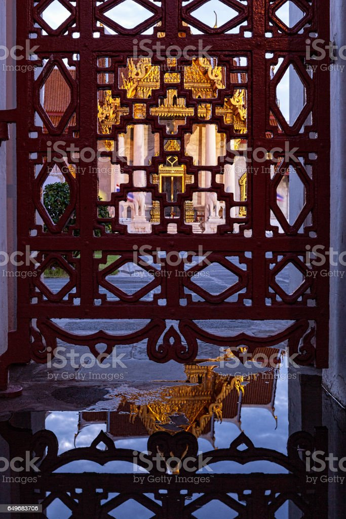 Reflection in a puddle and the gate of the front of Thai Buddhist temple of Wat Benchamabophit in the evening. stock photo