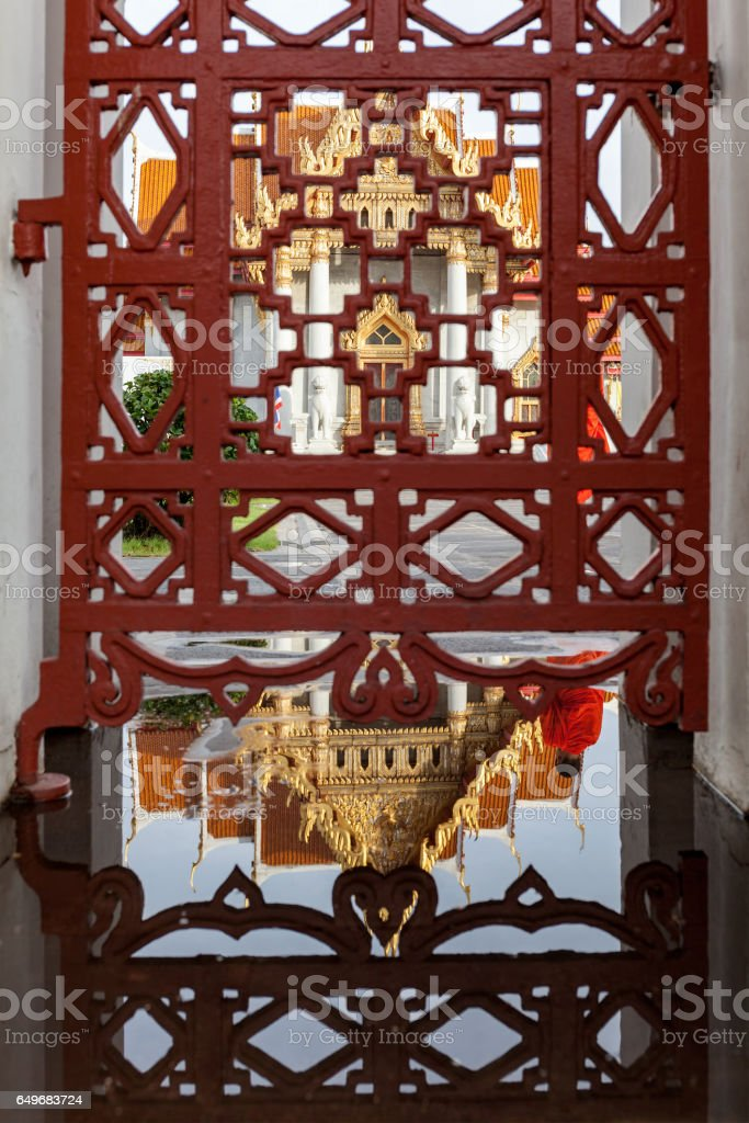 Reflection in a puddle and the gate of the front of Thai Buddhist temple of Wat Benchamabophit, in the early morning as a Thai Buddhist monk walks through the scene. stock photo