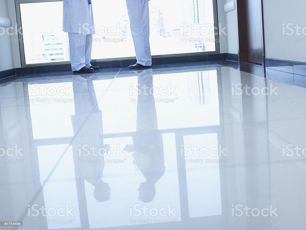 Reflection in floor of two doctors standing in hospital corridor stock photo