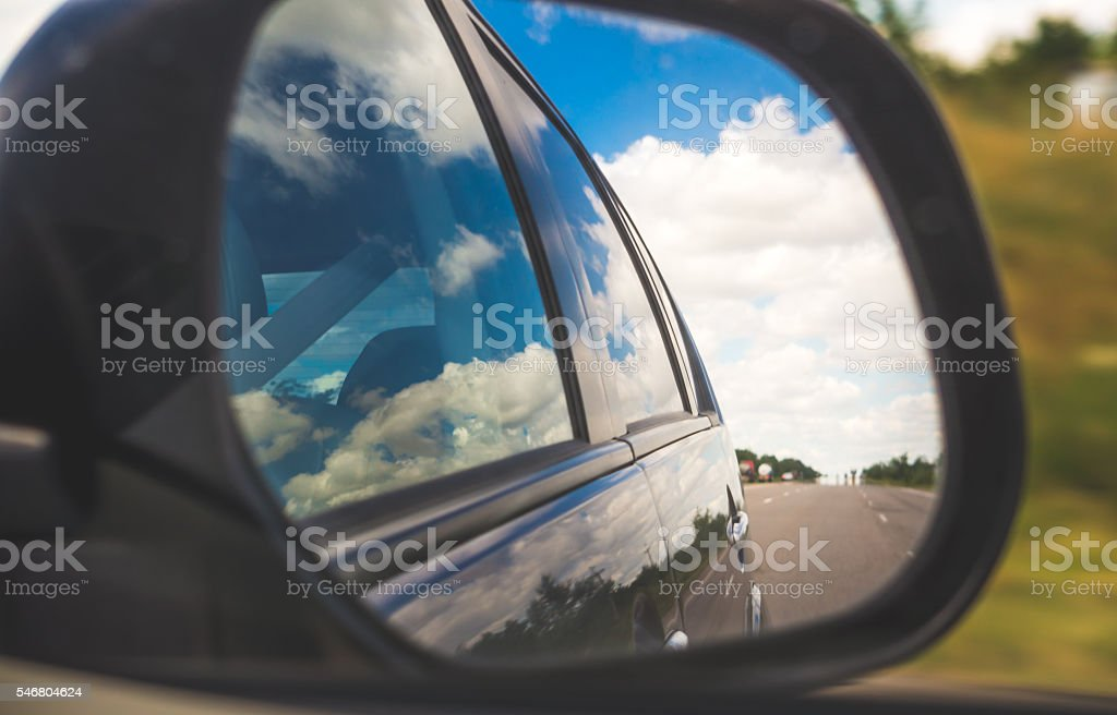 Reflection in the rear view mirror. Road trip stock photo