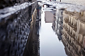 Reflection in water puddle of street in soho, nyc