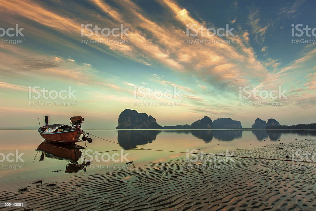 Reflection long tail boat at twilight on the beach stock photo