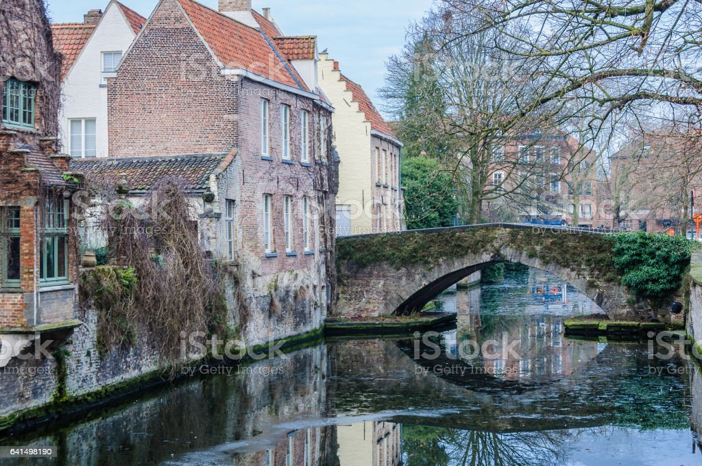 Reflection of a bridge in the canal in the Old Town of Bruges, Belgium stock photo
