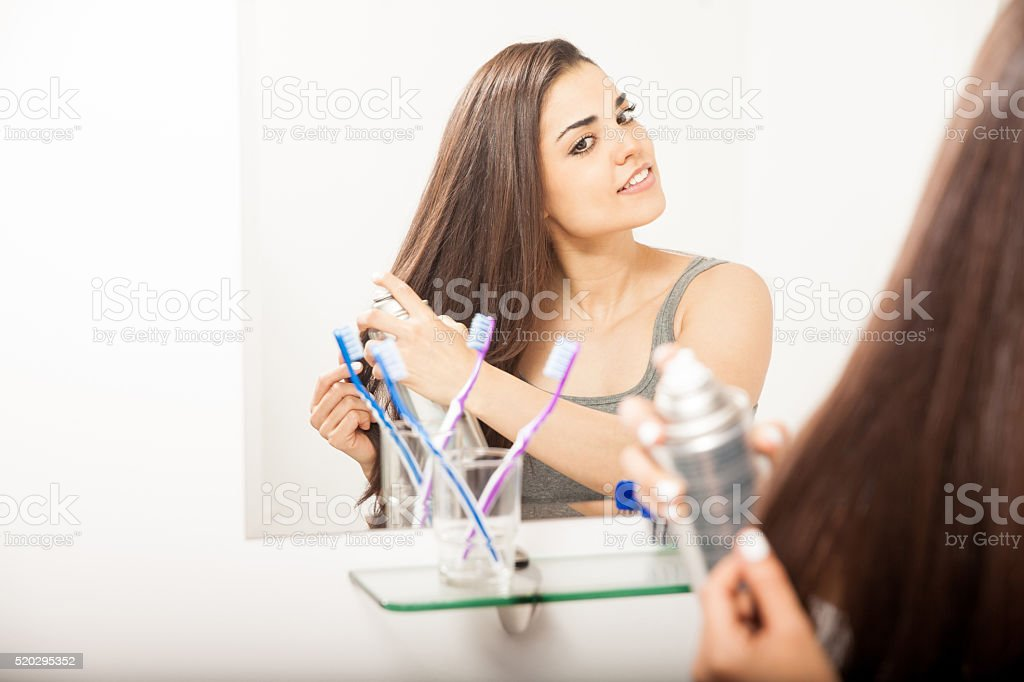 Reflection of a brunette styling her hair with spray stock photo