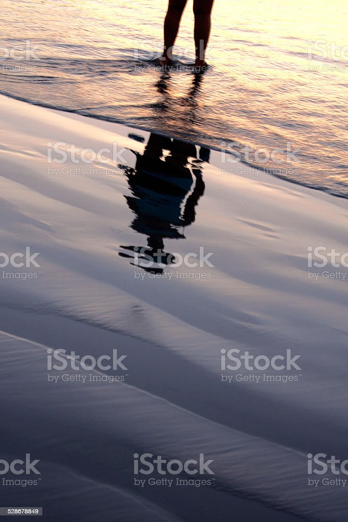 reflection of a person standing in ocean water stock photo
