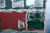 Reflection of a red and grey boathouse