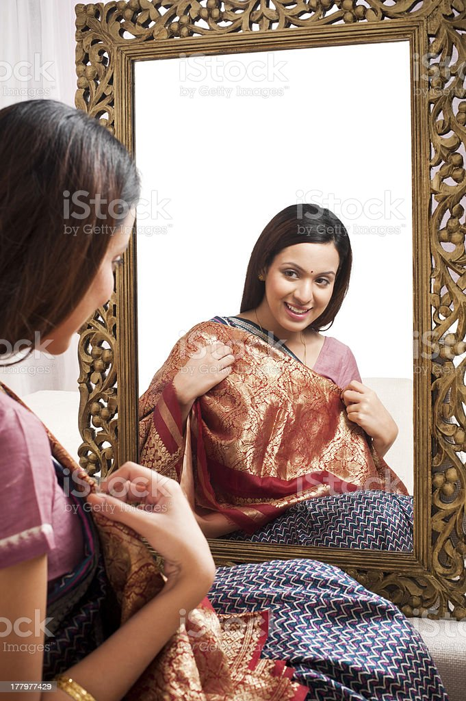 Reflection of a woman in mirror trying sari royalty-free stock photo