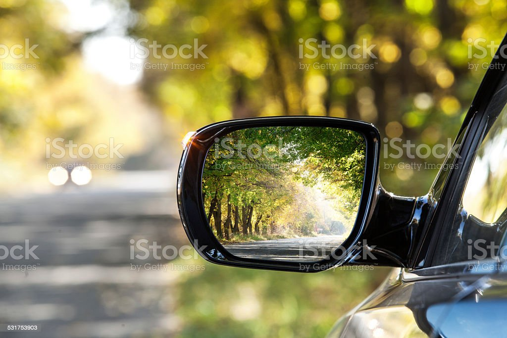 Reflection of autumn road at the rear view mirrow. stock photo