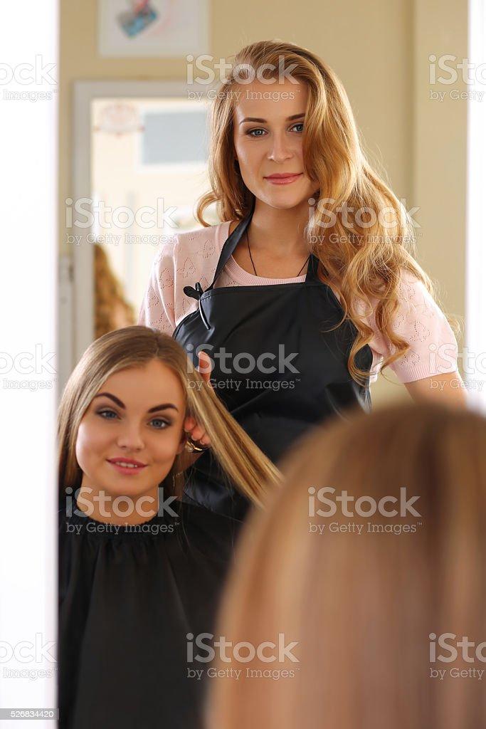 Reflection of beautiful blonde female hairdresser stock photo