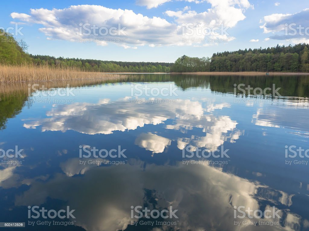 Reflection of blue sky with clouds in a lake stock photo