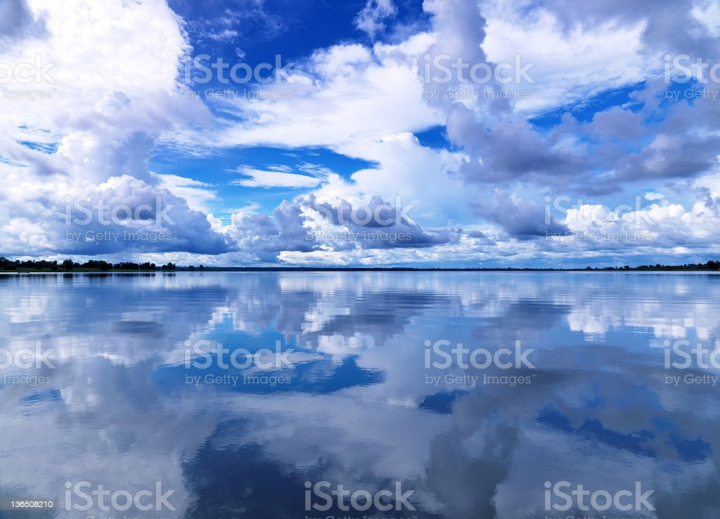 Reflection of blue sky with white clouds in water royalty-free stock photo