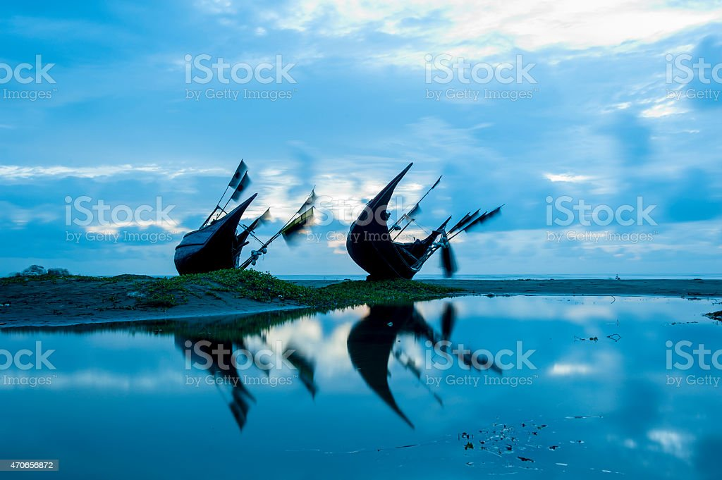 Reflection of boats in pool water on beach stock photo