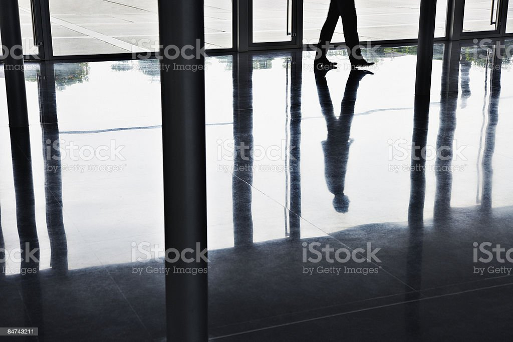 Reflection of businessman walking in office lobby royalty-free stock photo